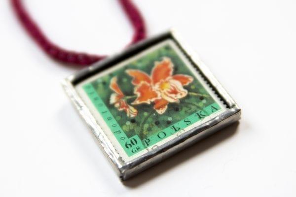 Dzikie Twory - naszyjnik ze znaczkiem pocztowym kwiat odontonia zbliżenie